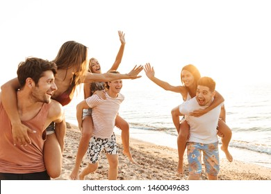 Group of cheerful happy young friends having fun at the beach, walking along the seashore, piggyback ride