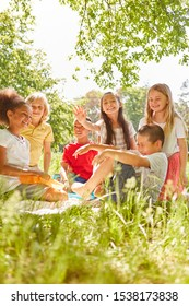 Group of cheerful kids is picnicking on a meadow in summer