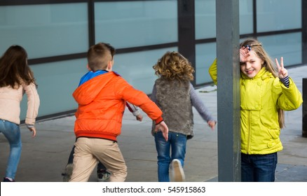 Group of cheerful kids playing hide-and-go-seek in street