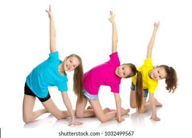 A group of cheerful little girls-gymnasts performing various gymnastic and fitness exercises. The concept of an active way of life, a happy childhood. Isolated on white background.