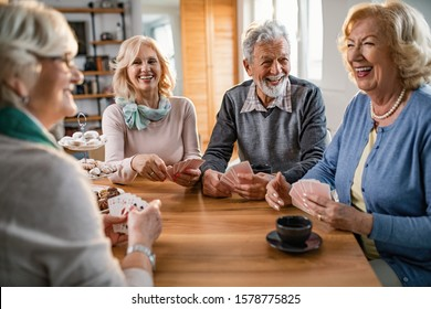 Group of cheerful mature people having fun while playing cards at home. Focus is on man.