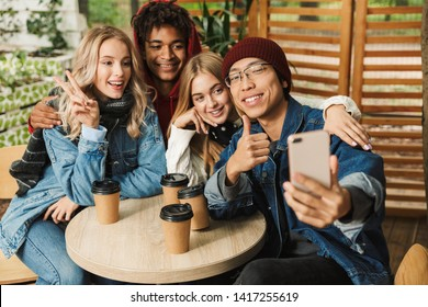Group if cheerful multiethnic friends teenagers spending fun time together outdoors, drinking coffee while sitting at the cafe and taking a selfie
