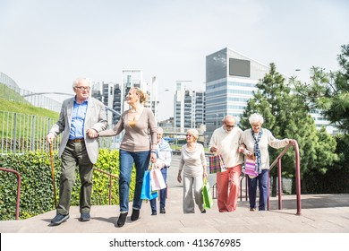 Group of cheerful pensioners having a walk outdoors and shopping in city centre - Senior group of friends bonding and having fun