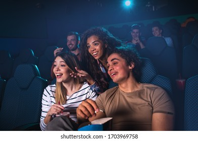 Group of cheerful people laughing while watching movie in cinema.