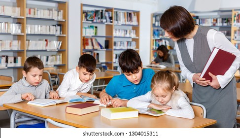Group of cheerful positive school kids studying in school library with friendly female teacher