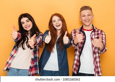 Group of cheerful school friends showing thumbs up while standing together over yellow background
