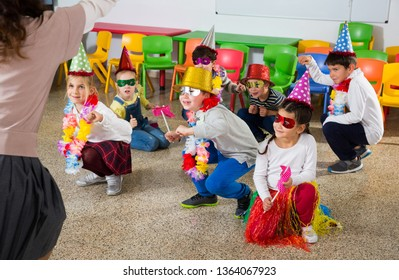 Group of cheerful school kids wearing festive hats having fun with their teacher during celebrating of holiday at school