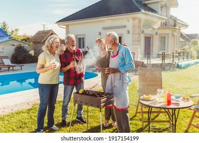 Gruppe von fröhlichen Senioren-Freunden, die sich auf der Grillparty im Garten am Pool amüsieren, sich um den Grill versammeln, Fleisch grillen und sonnigen Frühlingstag im Freien genießen