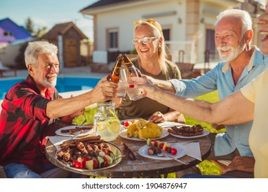 Group of cheerful senior friends making a toast while having an outdoor lunch in the backyard by the pool, gathered around the table, having fun spending time together