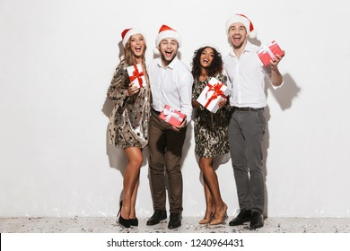 Group of cheerful smartly dressed friends celebrating New Year isolated over white background, holding gift boxes