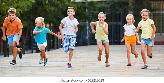 Group of cheerful smiling glad children running outdoors in city street on good weather