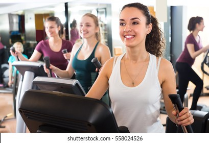 Group of cheerful smiling women using cross-trainers in sport club . Selective focus