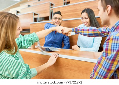 Group of cheerful students teaming up bumping fists in modern college auditorium, focus on laughing Middle-Eastern man and pretty Asian woman