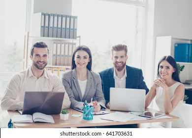 Group of cheerful successful young business people welcoming in their company`s sunny workspace. All wearing formal wear