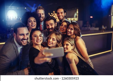 Group of cheerful taking selfie at the club