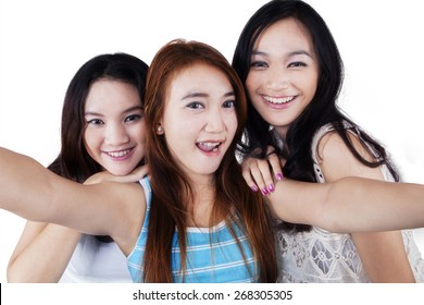 Group of cheerful teenage girls taking a selfie together in the studio, isolated over white