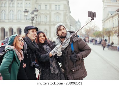 Group Of Cheerful Tourists Taking Selfie Using Smart Phone And Monopod