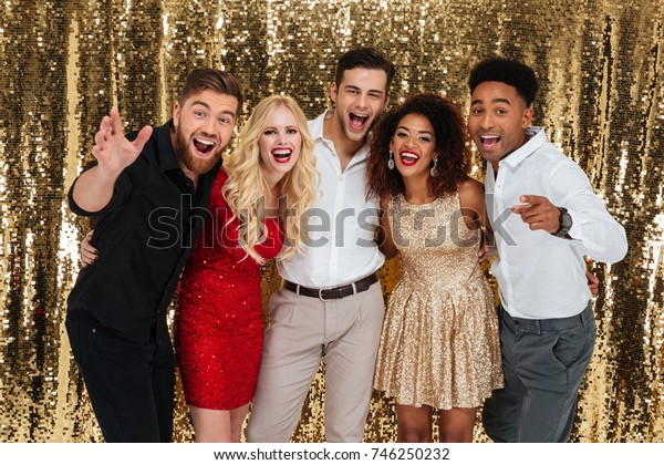 Group of cheerful well dressed people celebrating new year together isolated over shiny golden background