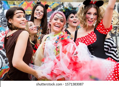 Group of cheerful women in sexy costumes at carnival party