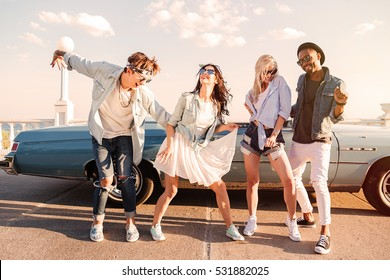 Group of cheerful young friends dancing together outdoors