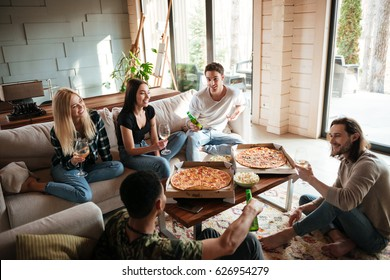 Group of cheerful young friends eating pizza and talking in living room at home