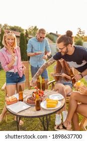 Gruppen fröhlicher junger Freunde versammelten sich um den Tisch, aßen gegrilltes Fleisch, trinken Bier und amüsieren sich auf einer Grillparty im Garten