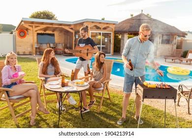 Gruppe von fröhlichen jungen Freunden, die sich beim Gitarrenspielen und beim Grillabend im Hinterhof, beim Biertrinken, Grillen und beim Entspannen am Pool amüsieren