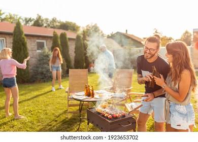 Gruppe von fröhlichen jungen Freunden, die eine Grillparty im Garten haben, Fleisch grillen, Toast machen, Bier trinken und sich an einem sonnigen Sommertag amüsieren
