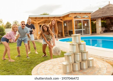 Group of cheerful young friends having fun playing the knock down tin cans by throwing a ball game while at poolside summertime outdoor party