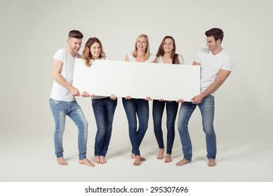 Group of Cheerful Young Friends Holding Blank White Board with Text Space Together on Off-White Background.