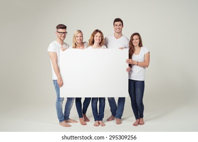Group of Cheerful Young Friends Showing Large White Board with Copy Space Against Off-White Background Inside the Studio.