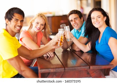 group of cheerful young friends toasting in a bar