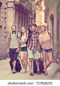 Group of cheerful young friends walking through the city with travel bags. Selective focus