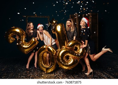 Group of cheerful young girls in Santa hats carrying gold colored numbers and throwing confetti