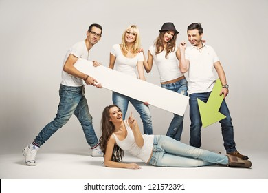 Group of cheerful young people holding empty board