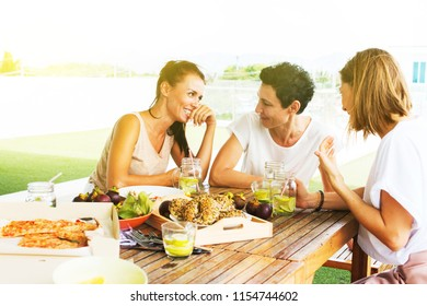 Group of cheerful young people women and children have open air picnic on terras. Pizza snack tropical fruits mangosteen orange healthy donuts summer cool drink with lime on wooden table Toned Banner