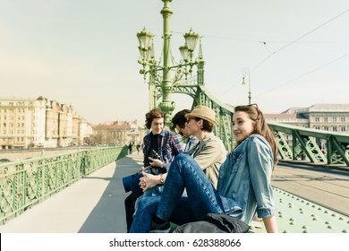 a group of cheerful young travelers, enjoying the beautiful sunny day during a break sitting on a bridge