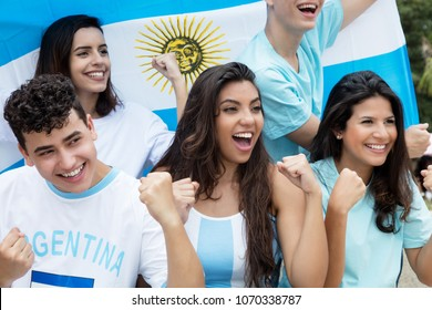 Group of cheering soccer fans from Argentina with argentinian flag at stadium