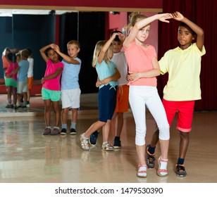Group of cheery kids dancing salsa dance in modern studio