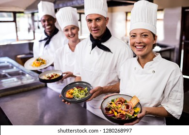 Group of chefs holding plate of prepared food in kitchen at hotel