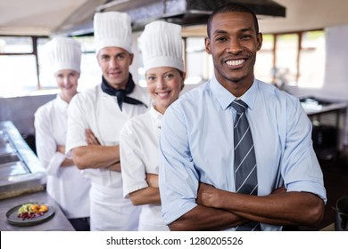 Group of chefs and manager standing with arms crossed in kitchen at hotel