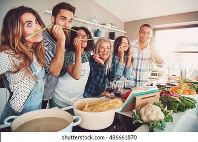 Group of chefs playing with asparagus stalks while standing in front of bowls of water, pasta and vegetables