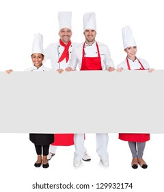 Group of chefs presenting empty banner. Isolated on white