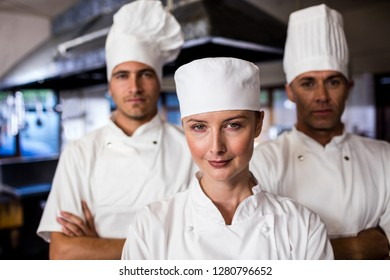 Group of chefs standing with arms crossed in kitchen at hotel