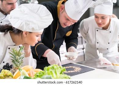 Group of chefs in white uniform preparing decorating food in restaurant kitchen
