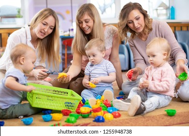 Group of children 1-2 years old playing in kindergarten or daycare centre under the supervision of moms