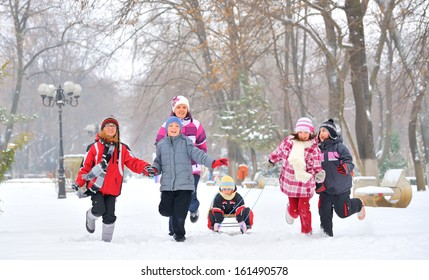group of children and adult playing on snow in winter time, young girl pulling sister through snow on sled