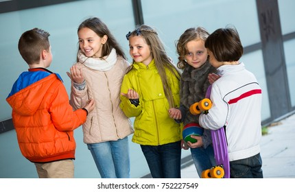 Group of children with ball and skateboard chatting outdoors