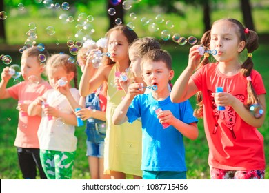 Group of children blowing soap bubbles