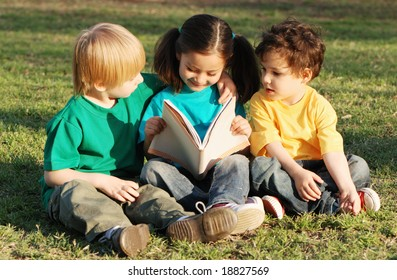 Group of children with the book on a grass in park with the book